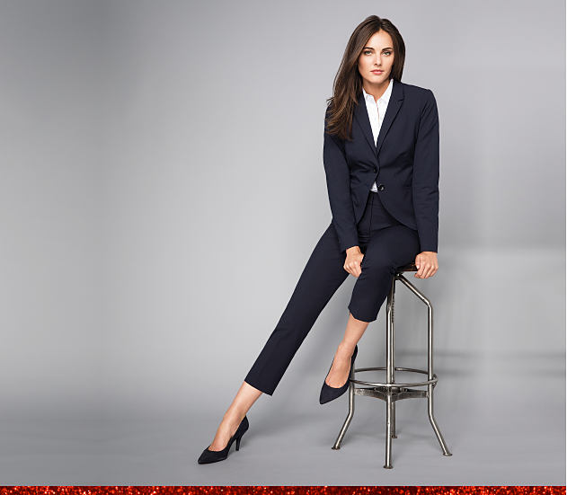 Woman wearing a navy suit sitting on a stool