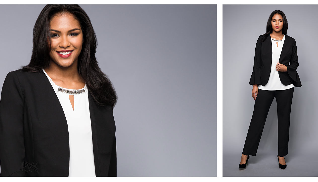 A woman wearing a black blazer over a white top and black pants.