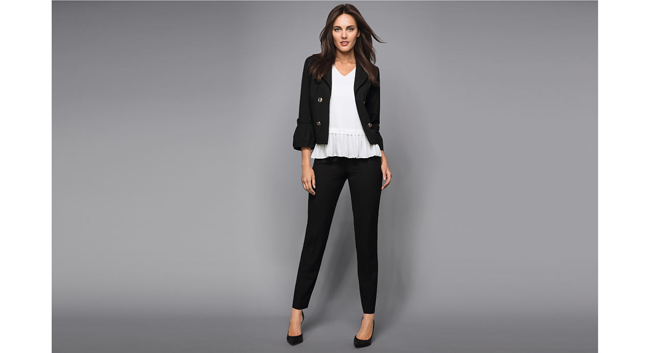 A woman wearing a black tie sleeve blazer over a white ruffle-hemmed shirt and black pants.