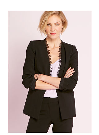 Model in black blazer with lace detail, pastel purple top, & black pants.
