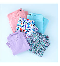 Folded pile of assorted pastel & printed pants.