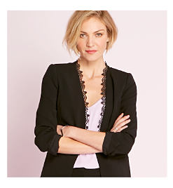 Model in black blazer with lace detail & pastel purple top.