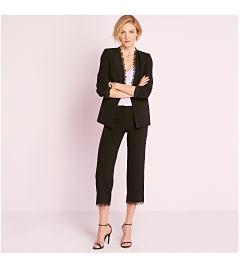 Model in black blazer with lace detail, pastel purple top, & black pants.