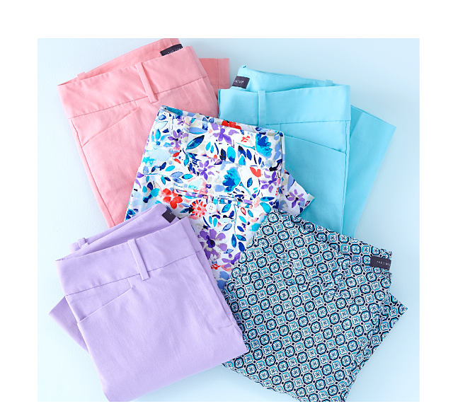 Stack of pants in a variety of prints & pastel colors.