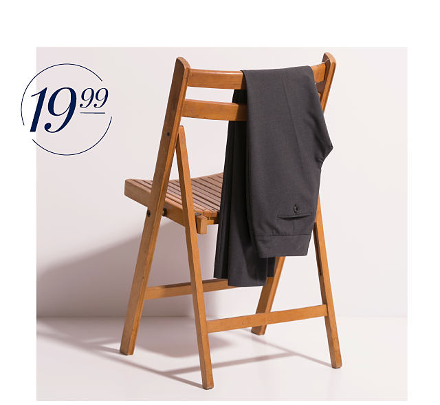A pair of charcoal signature pants draped over the back of a wooden folding chair.
