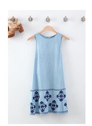 Light blue sundress with dark blue medallion print at hem hanging on wooden hanger.