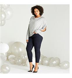 Model in grey sweater & dark jeans.