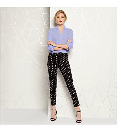 Model in periwinkle blouse & black pants