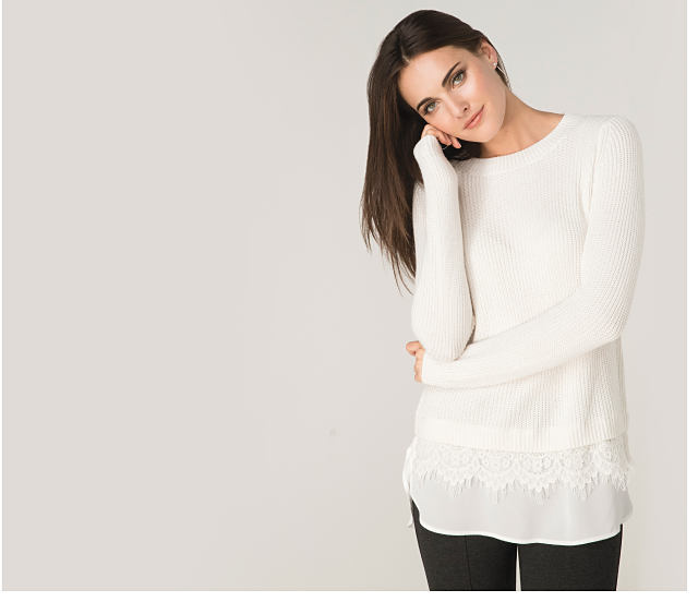 A woman wearing a white sweater with lace details