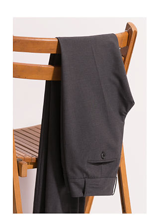 grey signature pant draped over a wooden chair