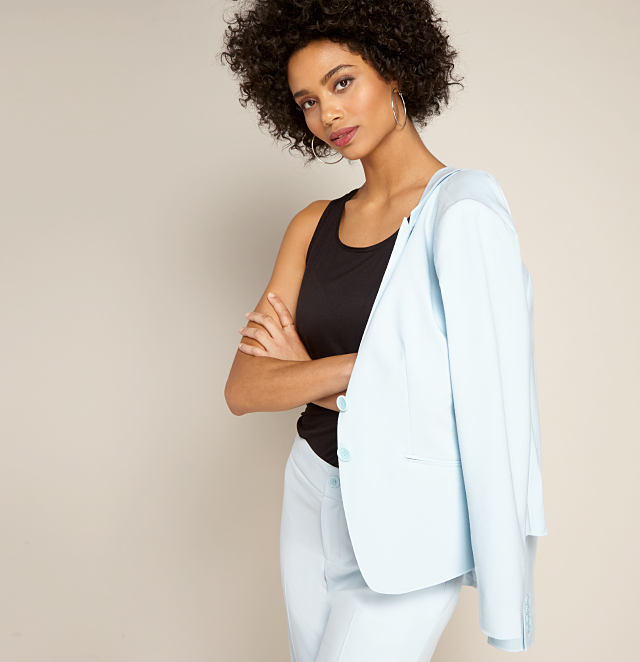 model in a black sleeveless top & light blue dress pants with a light blue suit jacket draped over one shoulder