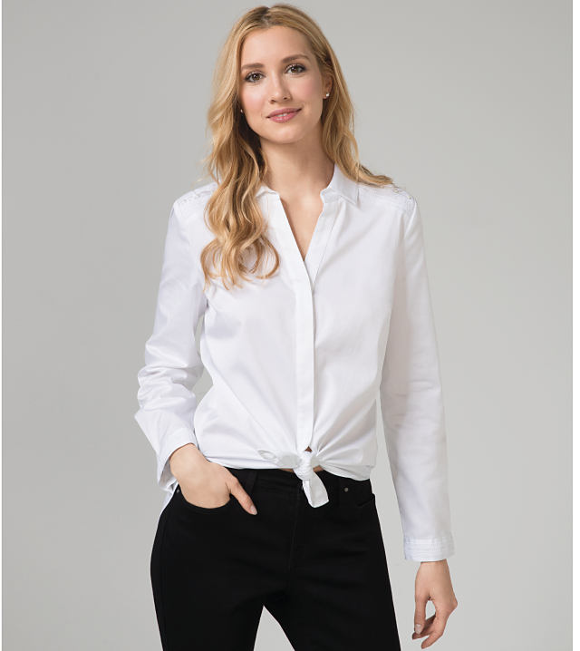 A woman wearing a white button-up and black pants
