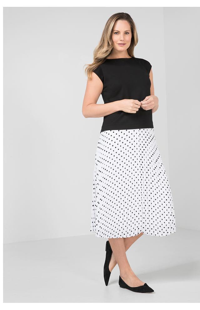 woman wearing black top and white polka dot dress