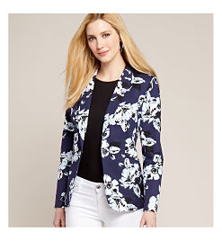 model in blue jacket with white floral print, black top, & white pants .