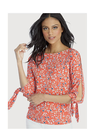 model in coral top with blue floral print & tie detail at elbows