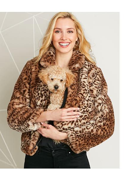 Model in leopard print jacket & black pants holding a puppy