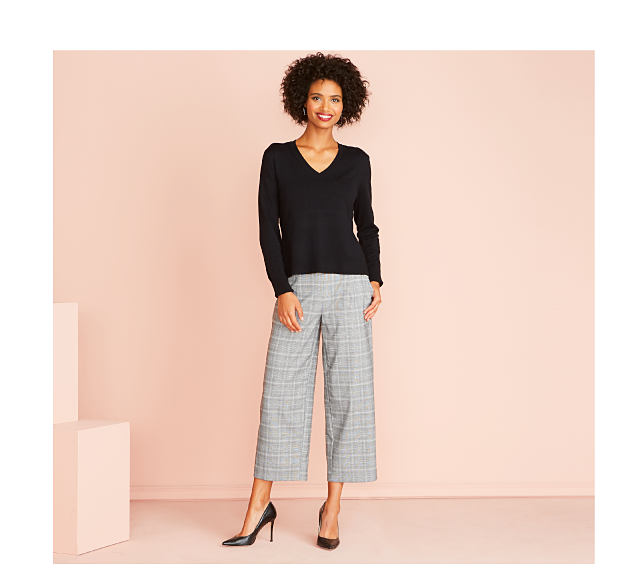 Woman in black top with plaid pants
