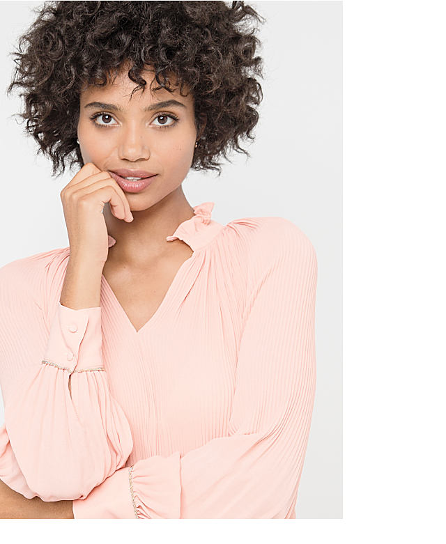A woman wearing a blush pink top with delicate pleating details.