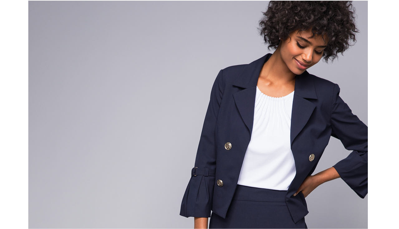 A woman wearing a navy tie sleeve jacket over a white shirt and pencil skirt.
